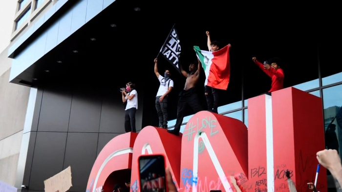 PROTESTERS IN ATLANTA MOUNT CNN SIGN AND RAISE BLACK LIVES MATTERFLAG